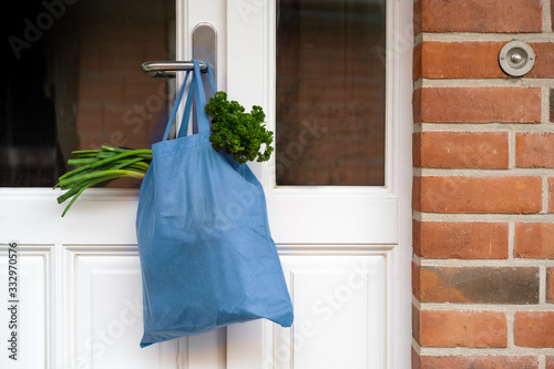 Fototapeta Blue shopping bag with fresh vegetables and goods was hanged on the front door, help concept during quarantine time because of coronavirus infection, copy space, selected focus obraz