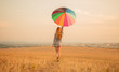 Stylish woman with umbrella walking in golden field