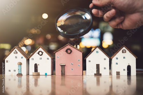 Fotomural Hand holding magnifying glass and looking at house model, house selection, real estate concept