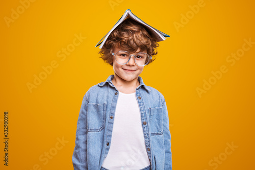Fotografie, Obraz Positive schoolboy with book and glasses