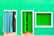 Leinwanddruck Bild - Window and door with green shutters on the green painted facade of the house. Colorful architecture in Burano island, Venice, Italy.