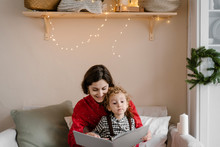 Mother And Son Reading Book On Christmas Day