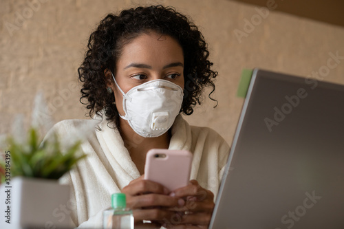Brazilian black woman wearing protective mask and holding smart phone at home office Wallpaper Mural