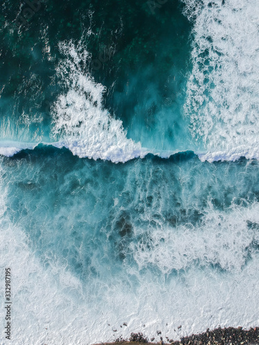 Leinwand Poster Aerial drone view of spashing waves in blue ocean