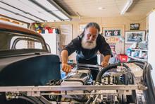 Senior Man Tinkering With His Car