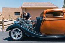 Retired Senior Man With His Orange Antique Car