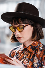 Close Up Of Stylish Brunette Woman Looking At The Books On The Street