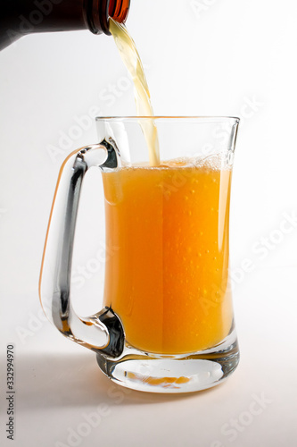 Beer pouring from bottle into mug or stein фототапет