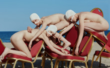 Side View Of Naked Women Leaning On Stack Of Theater Chairs On Beach