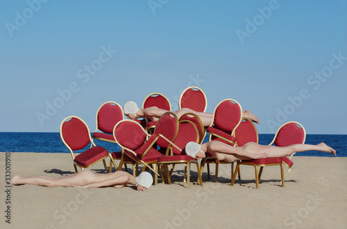 Naked women with theater chairs on beach - 333001910