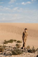Pretty Brunette Woman Walking In Desert Among Plants.