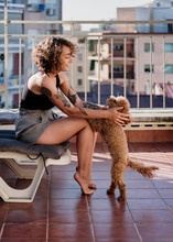 Woman With His Adorable Caniche Puppy