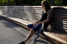 Skater Resting On Bench In Park