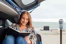 Woman Writes Near Ocean