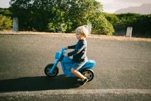 Boy Riding Toy Bike On Road