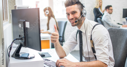 Photo Friendly online customer support agent with headset showing thumb up in call cen