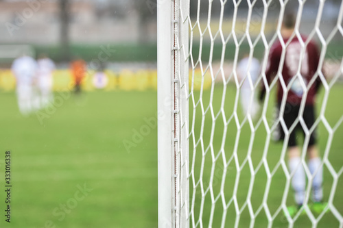 Photographie Detail of goal's post with net and football goalkeeper in the background