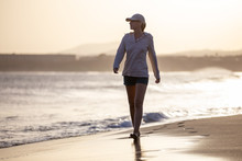 Young Woman Walking Along Ocean Beach With Waves