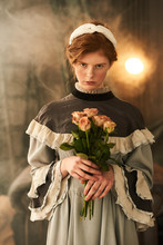 A Portrait Of A Beautiful Woman Dressed In An Old Dress Holding Roses