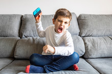 Excited Boy Playing Video Games At Home