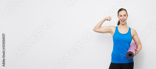 Obraz Portrait of young fit and sporty woman showing her strength from her yoga training, stading on a plain backdrop with capyspace  - fototapety do salonu