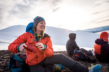 Woman Laughing With Coffee Maker While Outside In Iceland Snow