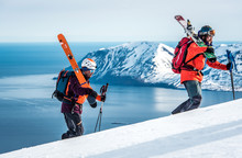 Men Hiking Uphill With Skis And Ocean And Mountain Behind Them