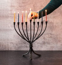 Woman's Hand Placing A Lit Candle In A Menorah For Hanukkah.
