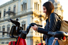 Woman Taking A Rental Electric Bike With Her Cell Phone.