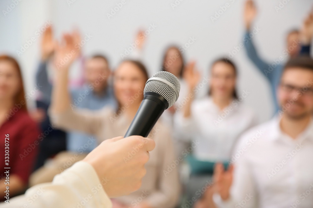 Fototapeta Business trainer with microphone answering questions indoors, closeup