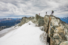 Three Climbers Stand On A Rock...