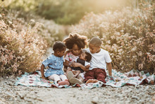 Four Happy Siblings Sitting On Blanket In Backlit Field Together