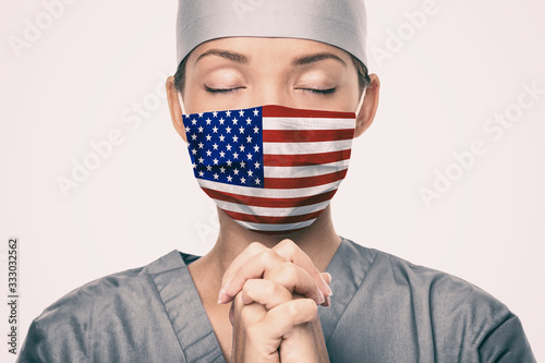 Fototapeta Coronavirus pandemic in the United States of America. USA american flag print on doctor's mask praying with claspeds hands in hope for help. Crying for help, disaster aid needed in the US. obraz