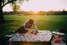 Mother Sits On Picnic Blanket ...