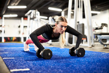 A Woman Doing Push Ups On The Turf In The Gym.