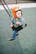 Little Boy With Fox Hat Swinging At The Playground.