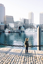 Photo Of A Boy At The Boston Harbor During A Sunset.