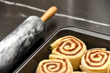 A Pan Of Raw, Homemade Cinnamon Buns Ready To Be Baked, With A Marble Rolling Pin In The Background With Copy Space