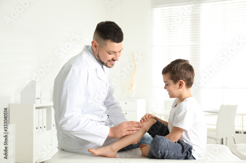 Professional orthopedist examining little patient's leg in clinic