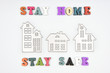Words Stay home Stay safe made from wooden letters and three metalic houses, concept of self quarantine at home as preventative measure against corona virus Covid 19 outbreak.