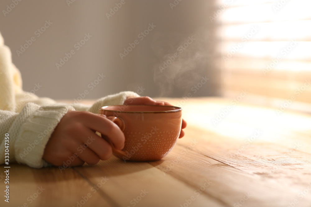 Fototapeta Woman with cup of tasty coffee at wooden table, closeup. Good morning