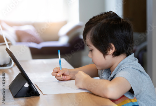 Fototapeta School kid self isolation using tablet for his homework, Child doing homework by using digital tablet searching information on internet during covid-19 lock down.Distance learning online education obraz