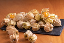 Ripe Physalis Isolated On A Wooden Background. Physalis Peruviana