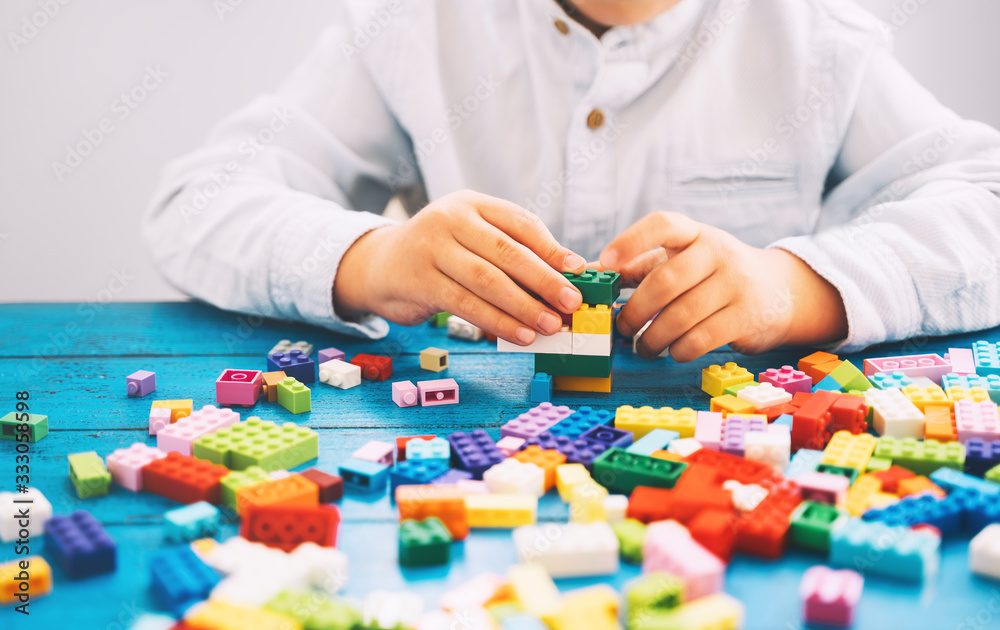 Child playing and building with colorful toy bricks, plastic blocks.