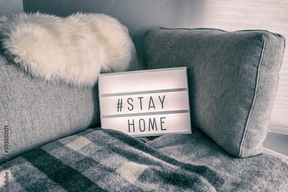 Fototapeta Coronavirus home lightbox sign with hashtag message #STAYHOME glowing on home sofa with cozy lambswool fur, blanket. COVID-19 text to promote self isolation staying at home.