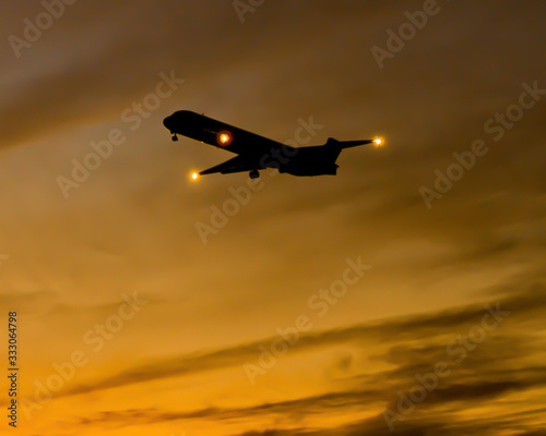 Photo Silhouette of passenger plane ascending against beautiful yellow orange sunset with wispy clouds at dusk