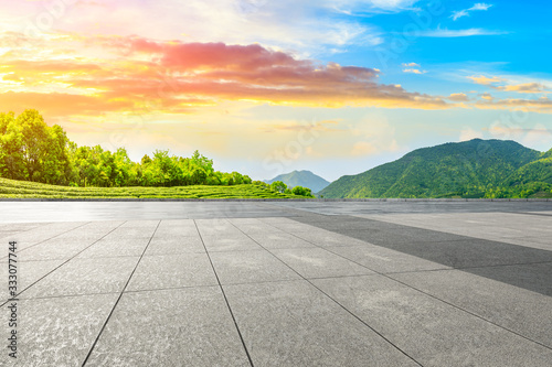 Empty square floor and green tea mountain nature landscape at sunset.