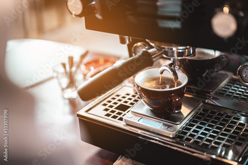 Fotografie, Obraz Close-up coffee maker that is professionally extracting coffee by barista with a deep white glass in the evening sun light