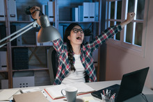 Young Happy Asian Japanese Woman Stay Up Late In Dark House Do Overtime Work On Homework. Cheerful College Girl Laughing And Screaming After Finish Project. Student Celebrating Raising Arms In Air.