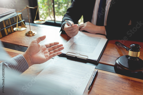 Canvastavla Lawyer working with client discussing contract papers with brass scale about legal legislation in courtroom, consulting to help their customer